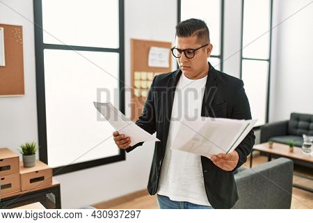 Young latin businessman with serious expression reading paperwork standing at the office.