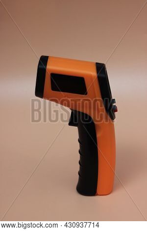 Infrared Thermometer (thermometer Gun) For Measuring Temperature Over Yellow Background. Covid-19 Sp