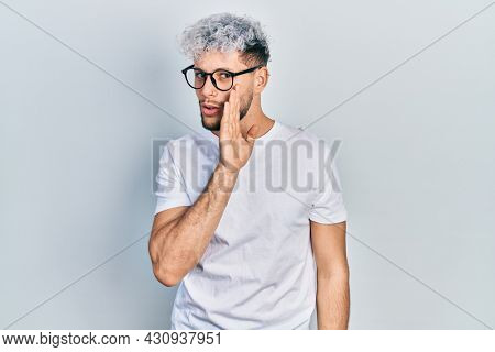 Young hispanic man with modern dyed hair wearing white t shirt and glasses hand on mouth telling secret rumor, whispering malicious talk conversation