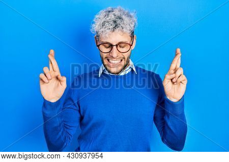 Young hispanic man with modern dyed hair wearing sweater and glasses gesturing finger crossed smiling with hope and eyes closed. luck and superstitious concept.