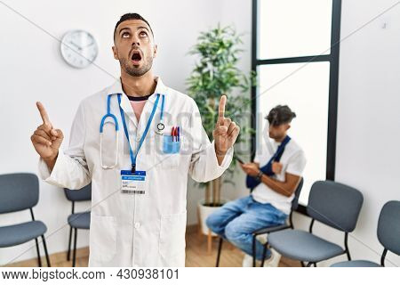 Hispanic doctor man at waiting room with pacient with arm injury amazed and surprised looking up and pointing with fingers and raised arms.