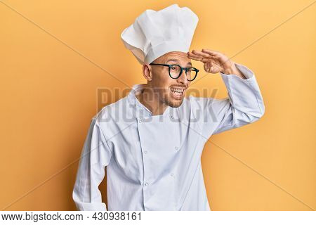 Bald man with beard wearing professional cook uniform very happy and smiling looking far away with hand over head. searching concept.
