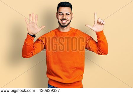 Young hispanic man with beard wearing casual orange sweater showing and pointing up with fingers number seven while smiling confident and happy.
