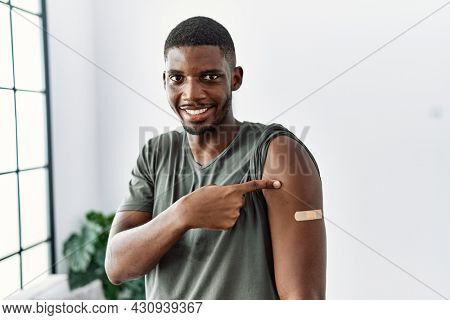 Young african american man getting vaccine showing arm with band aid smiling happy pointing with hand and finger