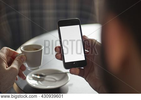 Businessman With A Cup Of Coffee And A Phone With Copyspace In His Hand