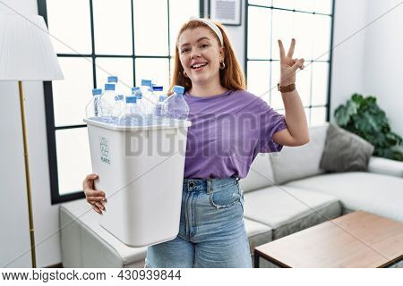 Young redhead woman holding recycling wastebasket with plastic bottles smiling looking to the camera showing fingers doing victory sign. number two.