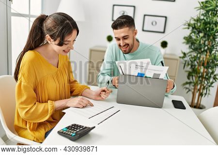 Young couple controlling family economy at home.