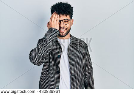 Young arab man with beard wearing glasses covering one eye with hand, confident smile on face and surprise emotion.
