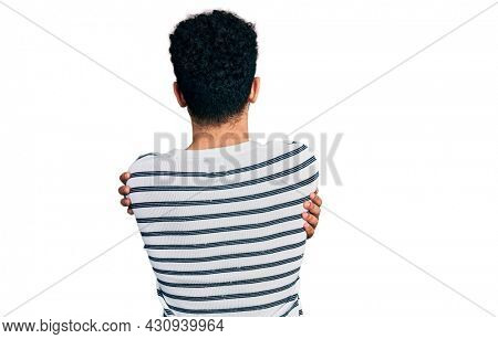 Young arab man with beard wearing casual striped sweater hugging oneself happy and positive from backwards. self love and self care