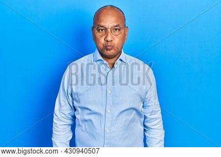 Middle age latin man wearing casual clothes and glasses puffing cheeks with funny face. mouth inflated with air, crazy expression.