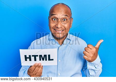 Middle age latin man holding html paper message pointing thumb up to the side smiling happy with open mouth
