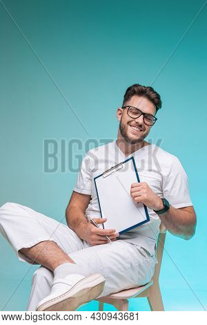 Laughing Optimistic Male Physician Practitioner In Glasses Hold Blank Space Sheet. Studio Portrait O