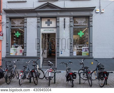 Brugge, Flanders, Belgium - August 4, 2021: Gray Painted Facade Of Pharmacy Neyt With Bunch Of Bikes