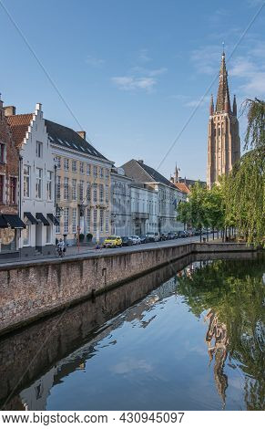 Brugge, Flanders, Belgium - August 4, 2021: Quiet Dijver Canal Reflecting Notre Dame Cathedral Tower