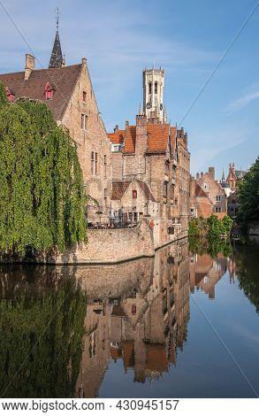 Brugge, Flanders, Belgium - August 4, 2021: Sunlit Belfry Towers Over Brown Brick Back Facades, Mirr
