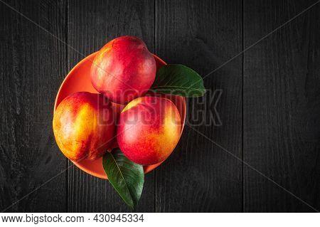 Three Red Ripe Nectarine Hybrids In Their Ripening Season Lie On Orange Plate Or On A Dark Vintage T
