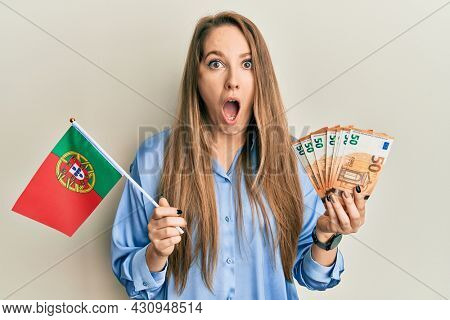 Young blonde woman holding portugal flag and euros banknotes afraid and shocked with surprise and amazed expression, fear and excited face.