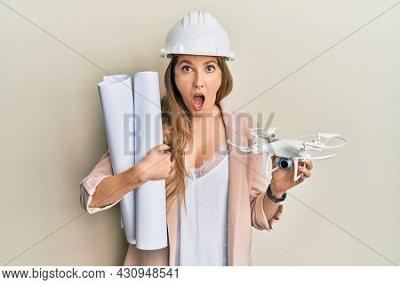 Young blonde woman wearing safety helmet holding blueprints and drone afraid and shocked with surprise and amazed expression, fear and excited face.
