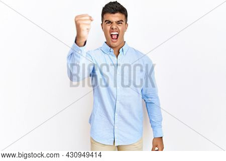 Young hispanic man wearing business shirt standing over isolated background angry and mad raising fist frustrated and furious while shouting with anger. rage and aggressive concept.