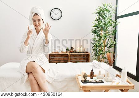 Young blonde woman wearing bathrobe at wellbeing spa showing and pointing up with fingers number seven while smiling confident and happy.