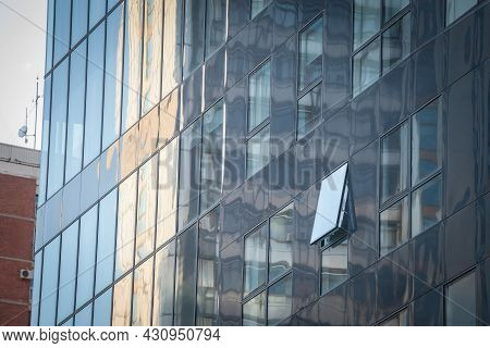 Abstract Facade Of A Finance Business Building With Mirror Windows, Some Of Them Being Opened To Let