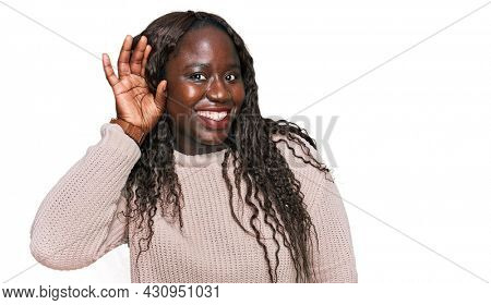 Young african woman wearing wool winter sweater smiling with hand over ear listening an hearing to rumor or gossip. deafness concept.