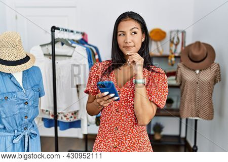 Young hispanic woman working at retail boutique using smartphone with hand on chin thinking about question, pensive expression. smiling and thoughtful face. doubt concept.