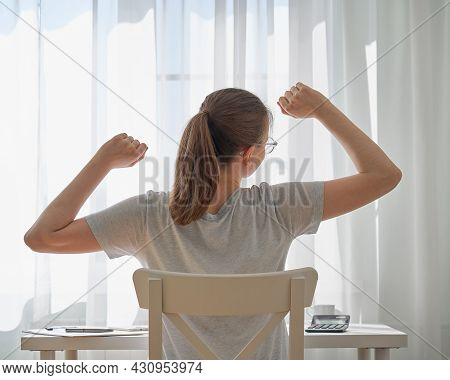 Back View Of Faceless Young Woman Stretching And Having Back Pain After Long-hours Working From Home