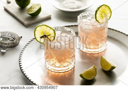 Refreshing Margarita Mocktails With Salted Rims And Garnished With Lime Slices, Ready For Drinking.