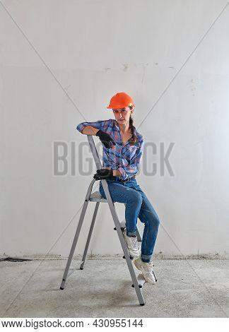 Female Builder In Hard Hat Sits On A Stepladder