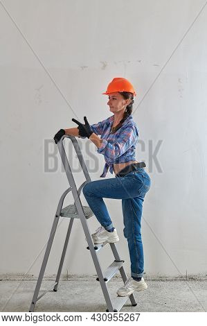 Cheerful Girl In Orange Hard Hat And Jeans On A Stepladder