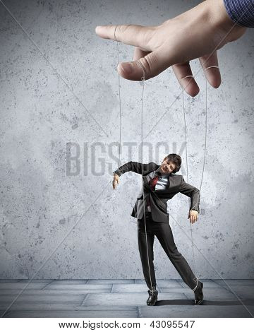 Businessman marionette on ropes controlled by puppeteer poster