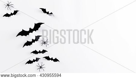 Top View Of Halloween Crafts, Black Paper Ghost, Spider And Bats Flying Over White Background With C