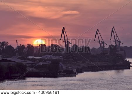 Gorgeous Ruby Sunset On The Ob River. Big Yellow Sun Disc. Silhouette Of A Cargo Port Crane. Houses