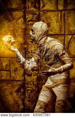 Ancient Egyptian mythology. Scary evil mummy stands by an ancient Egyptian tomb and holds a skull. Halloween.