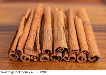 Close Up Shot Of Aromatic Dry Cinnamon Sticks On Wooden Table Background, Selective Focus