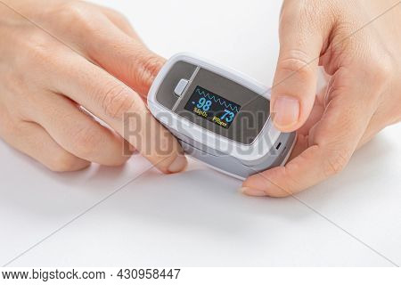 Close-up Of Woman Using Digital Pulse Oximeter On Person's Finger, To Check The Pulse Of Amount Of O