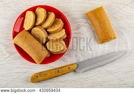 Sweet Creamy Sausage With Peanut (oriental Sweets), Slices Of Sweets In Red Saucer, Kitchen Knife On