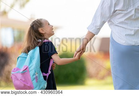Parent and pupil of primary school going hand in hand. Woman and girl with backpack behind the back. Beginning of lessons.