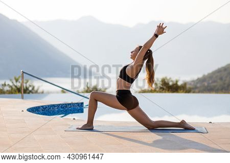 Young Woman Doing Vinyasa Yoga Routine In The Morning At The Resort Pool