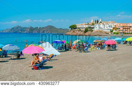 Aguilas, Spain - July 27, 2021: Some people are enjoying the beach in Calabardina Beach, in Aguilas, in the Costa Calida coast, Murcia, Spain
