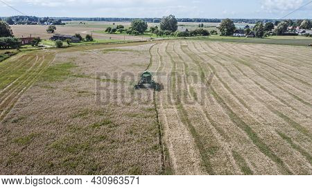 Harvest Time. Combine Harvester Harvests Barley In The Field In Summer Day. Aerial View.