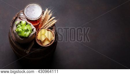 Lager beer mug, hops and wheat on old wooden barrel. With copy space