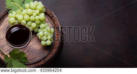 White grape and red wine glass on old wooden wine barrel. Top view flat lay with copy space