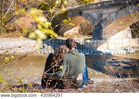 Autumn Walk. Rear View. Of Couple Sits On The River Bank. Man And Woman In Warm Clothing Looking At