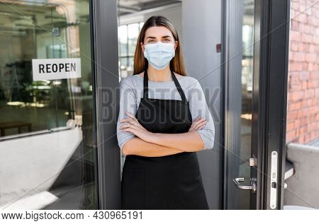 small business, reopening and service concept - woman in mask with reopen banner on window or door glass