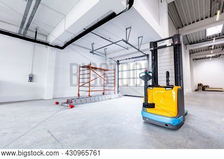 Pallet jack in new warehouse industrial hall with racking storage racks. Shelving system