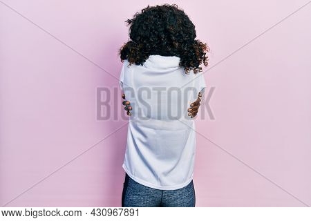 Young african american woman wearing sportswear and towel hugging oneself happy and positive from backwards. self love and self care