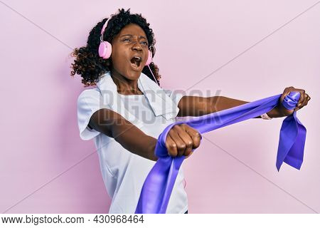 Young african american woman training arm resistance with elastic arm bands using headphones angry and mad screaming frustrated and furious, shouting with anger looking up.