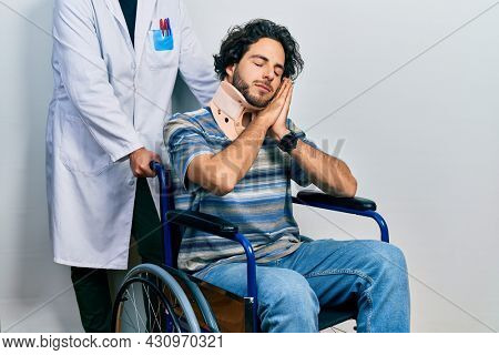 Handsome hispanic man sitting on wheelchair wearing neck collar sleeping tired dreaming and posing with hands together while smiling with closed eyes.